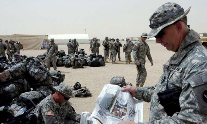 Sgt. 1st Class David Birkman reads a Stars and Stripes newspaperas he and several hundred Soldiers wait to leave Camp Buehring, Kuwait en route to Iraq in this April 2006 photo. (Photo by Clinton Wood/U.S. Army)