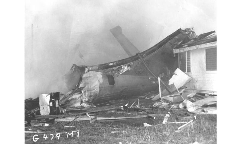 A damaged B-29 tail section leans against Capt. Bartley's home after crashing on Andersen Air Force Base, Guam, Dec. 17, 1953. The open ditching hatch is where 1st Lt. Jack Patton, radar officer, Airman 1st Class Bill Backman, tail gunner, and Airman 2nd Class Bob Jensen, electronic counter-measure operator, escaped. (U.S. Air Force photo/Released)