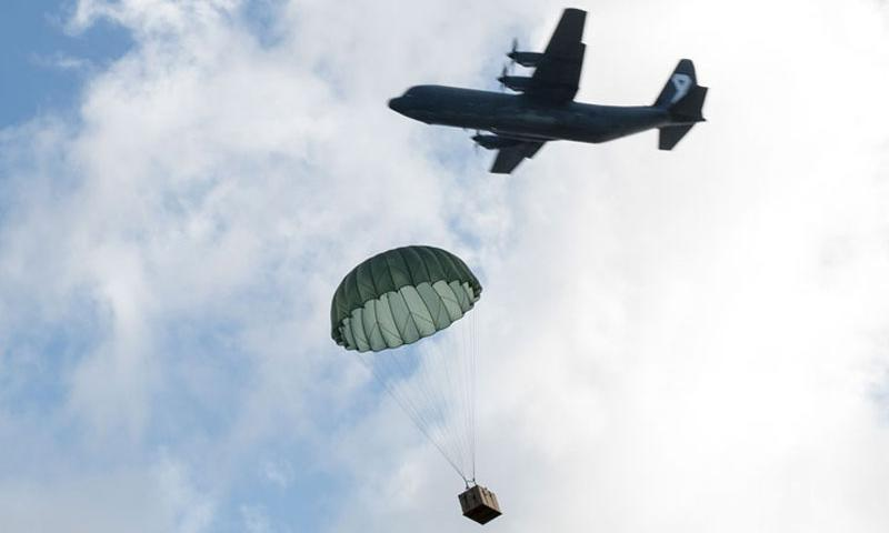 Royal Australian Air Force C-130J aircrew observe a U.S. Air Force C-130H low-cost, low-cost altitude bundle drop to Fais Island, Federated States of Micronesia, Dec. 8, 2015, during Operation Christmas Drop 2015. (U.S. Air Force photo by Osakabe Yasuo/Released)
