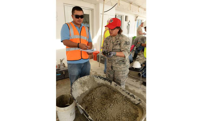 U.S. Air Force Staff Sgt. Ruth Aguon, Guam Air National Guard 254th RED HORSE Squadron, reviews concrete specifications with an American Concrete Institute instructor during a field concrete testing course in Mangilao, Guam, Dec 11, 2014. RED HORSE joined with U.S. Naval Base Guam Sailors and Department of Defense civilians to become certified in field testing concrete during a two-day course. (U.S. Air Force photo by Senior Airman Cierra Presentado/Released)