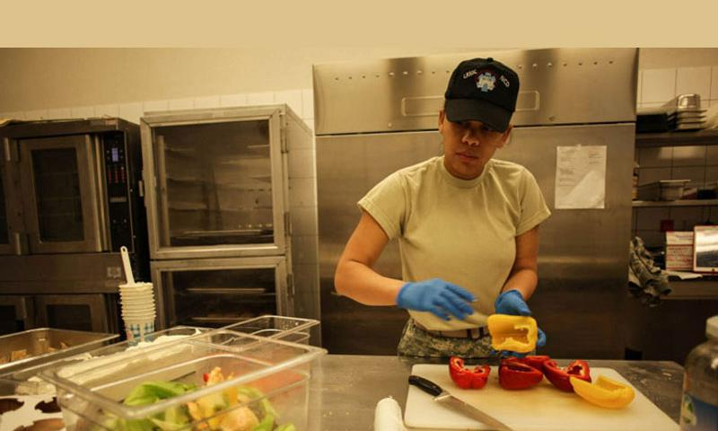 Pfc. Ninotchka TorresSenal, 26, a nutrition care specialist from Hampton, Va., prepares peppers in the kitchen at Landstuhl Regional Medical Center in Germany, the U.S. military's largest overseas hospital, on Tuesday, Dec. 23, 2014. For TorresSenal and many others at the hospital, Christmas is almost just another day at the office. (Matt Millham/Stars and Stripes)