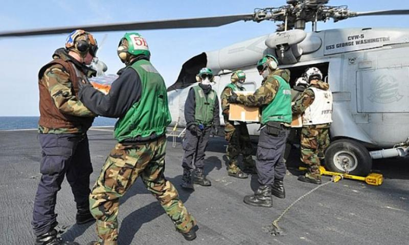 Sailors aboard USS Ronald Reagan, floating off the coast of Japan, load humanitarian relief supplies March 22, 2011, into a U.S. Navy Seahawk belonging to Helicopter Anti-Submarine Squadron 14, piloted by Lt. Cmdr. Ben Van Buskirk and Lt. Victoria Throckmorton. The pilots made several trips into tsunami-damaged towns along the coast to deliver the supplies. (T.D. Flack/Stars and Stripes)