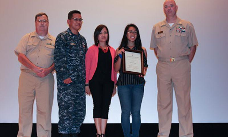 YOKOSUKA, Japan — Navy JROTC Cadet Master Chief Petty Officer Caycelyn Badiola proudly holds her Legion of Valor Bronze Cross for Achievement certificate on the Benny Decker Theater stage with her parents and Navy JROTC instructors during a Kinnick High School assembly. From left to right: retired Navy Lt. Cmdr. Kevin Mode, Chief Petty Officer Manual Badiola, Yvonne Badiola, Caycelyn Badiola and retired Navy Senior Chief Petty Officer Richard Kilanski stand together. (Photo courtesy of Robert Tiffany)