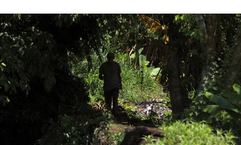 """In this still from the controvercial new film """"Unclaimed,"""" a man named Dang Tan Ngoc, living in Vietnam, can be seen walking through the trees near his home. The man claims he is John Hartley Robertson, an American soldier listed as killed in action in Vietnam in 1976. The film has pitted Robertson's family against the U.S. government who has said that DNA and figerprints prove the man is a fraud. The film premiere's at the G.I. Film Festival in Washington D.C. on May 12. Courtesy of Myth Merchant Films."""