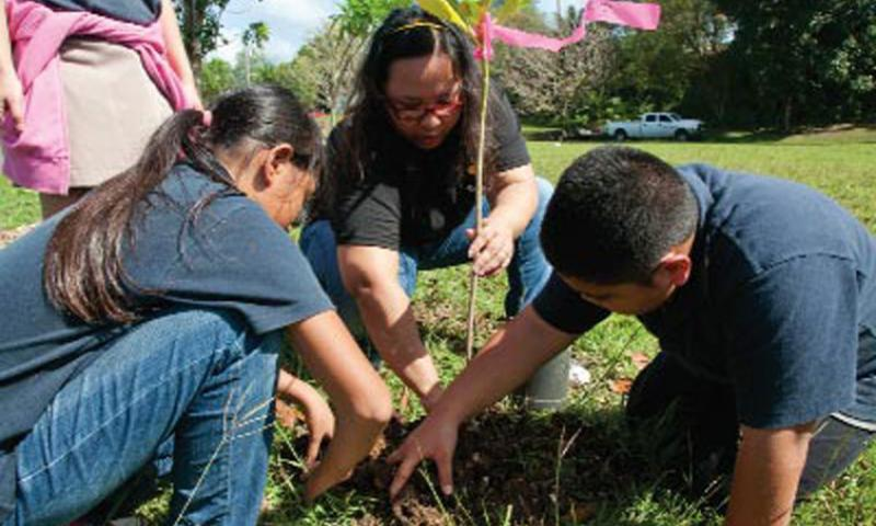 English as a Second Language teacher Grace Claros instructs a pair of students during a special tree-planting lesson in collaboration with Naval Facilities Engineering Command (NAVFAC) Marianas at Harry S. Truman Elementary School in Santa Rita Nov. 16. U.S. Navy photo by Shaina Marie Santos/Released