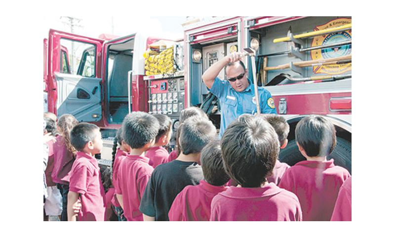 U.S. Naval Base Guam Fire and Emergency Services Lead Firefighter Carlos Presnell describes some of the tools used in emergency situations during a presentation at Capt. H.B. Price Elementary School in Mangilao Jan. 29. U.S. Navy photo by Shaina Marie Santos