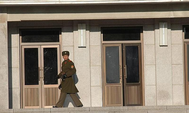 An unidentified North Korean soldier, binoculars in hand, keeps an eye on the South Korean side of the Joint Security Area of the Demilitarized Zone on Dec 22, 2011. Jon Rabiroff/Stars and Stripes