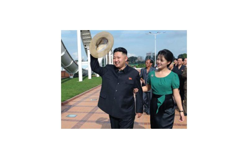 In this July 25, 2012, photo released by the Korean Central News Agency and distributed in Tokyo by the Korea News Service, North Korean leader Kim Jong Un, accompanied by his wife Ri Sol Ju, waves to the crowd as they inspect the Rungna People's Pleasure Ground in Pyongyang, North Korea. Korean Central News Agency via Korea News Service/file
