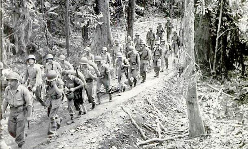 Marines march along a jungle track on Guadalcanal in November 1942. Catherine Ott's father, E. Gordon Bruce, is the first soldier in line at the extreme left of the picture.