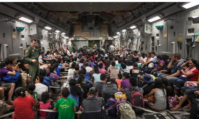 Displaced residents from Typhoon Haiyan prepare for takeoff inside a C-17 Globemaster from Tacloban Airport to Manila, Nov. 15, 2013. Evacuation and supply delivery are two of the ways U.S. military is working to assist Operation Damayan. Jonathan Wright/U.S. Marine Corps