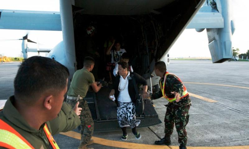 U.S. Marines guide a Filipino woman off an MV-22B Osprey and toward the terminal at Villamor Air Base Nov. 12, 2013. Typhoon Haiyan, the strongest typhoon recorded to make landfall has displaced hundreds of thousands in the Philippine Islands. STEPHEN D. HIMES/U.S. MARINE CORPS