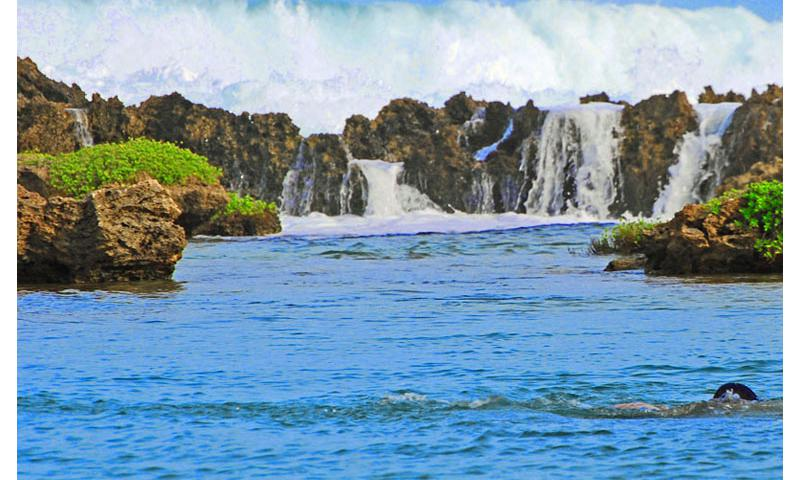 A swimmer enjoys Inarajan Salt Water Pool as the majestic waves of the Pacific Ocean turn tranquil after hitting the natural rock formations that help create it.