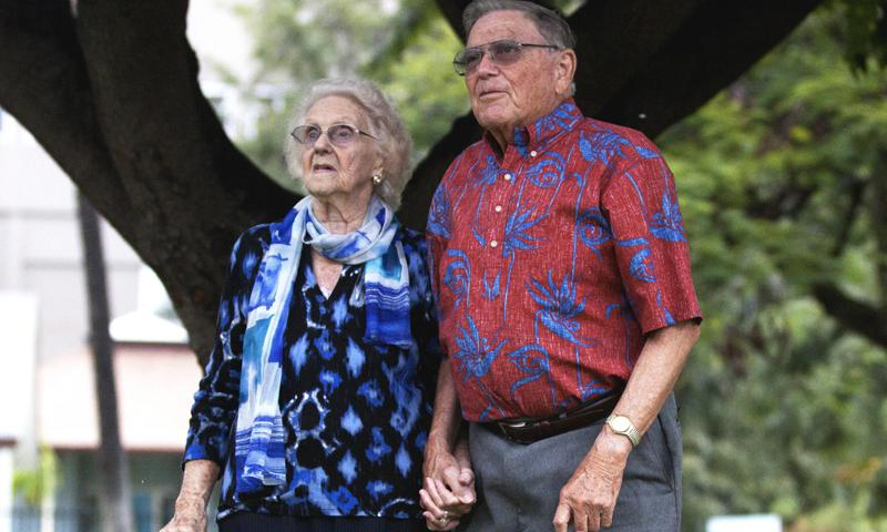 Walter and Myrtle Powers hold hands as they look at the mountains in the distance outside a chapel in Honolulu.  The couple served in World War II from 1943-45 and got married after they were discharged, resulting in a 66-year marriage.
