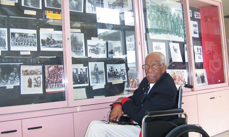 Tuskegee Airman Lt. Col Dryden in front of the LMS Tuskegee Airman Display Cabinet.