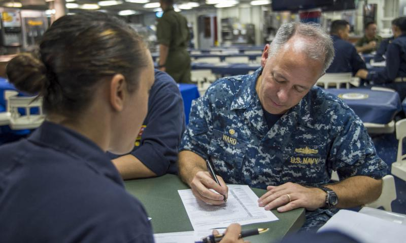 Capt. Jeffrey Ward, commander of the USS Bonhomme Richard, registers for an absentee ballot with help from Lt. j.g. Jessica Vaeth, the ship's voting assistance officer, while transiting the East China Sea, in August 2016. Jeanette Mullinax/U.S. Navy