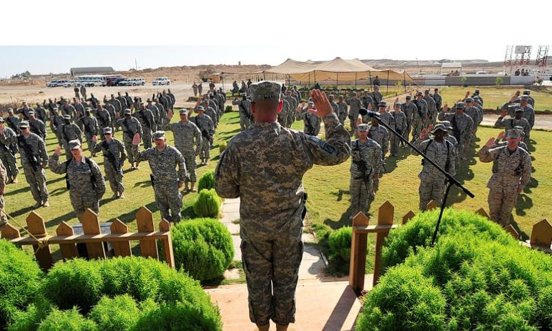 With hands raised, 126 U.S. servicemembers rehearse prior to a mass re-enlistment ceremony at Al Asad Air Base, Iraq, Oct. 5, 2011.  U.S. Air Force