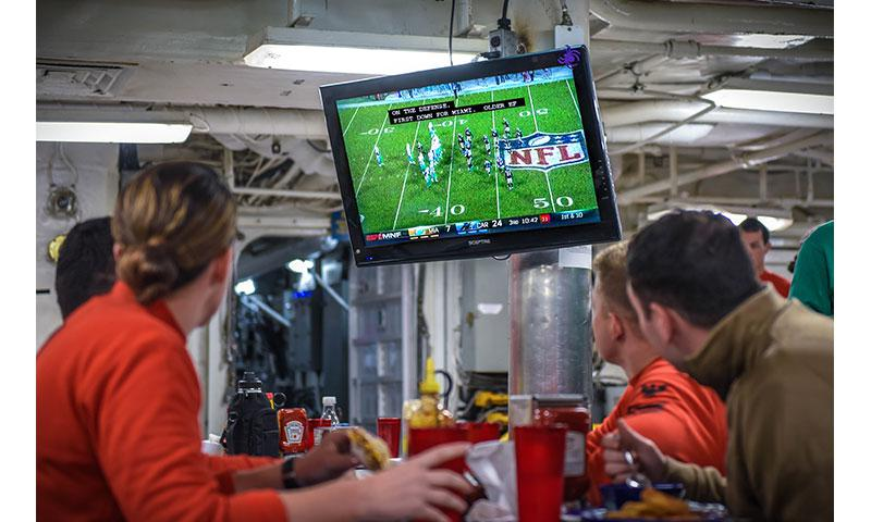PACIFIC OCEAN (Nov. 14, 2017) - Sailors watch football on the forward mess decks of USS Theodore Roosevelt (CVN 71) via the newly upgraded American Forces Network Direct-to-Sailor service.  AFN is transitioning to high definition broadcasting signal, starting with U.S. Navy ships in the Pacific Region and expects to complete the process for much of its worldwide audience by mid-December. (U.S. Navy photo by Mass Communication Specialist 3rd Class Alex Perlman/Released)