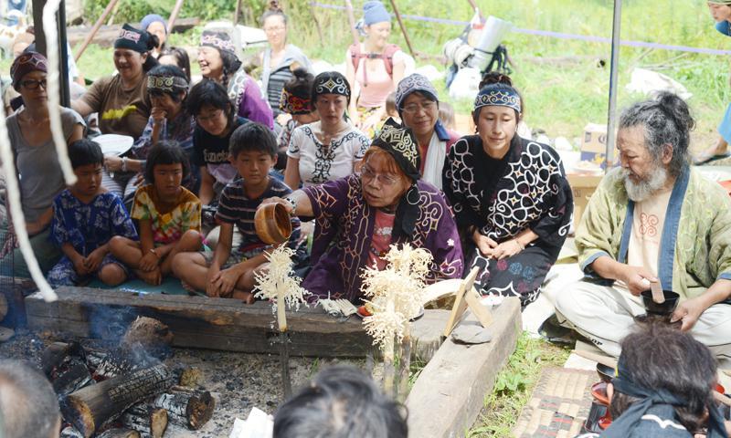 "Rera Asir, the organizer of Ainu Moshiri Festival, pours the scared rice wine onto the ""Inau,"" a ritual stick, during ""Kanuinomi,"" a ceremony addressing the Great Spirit, at the Ainu Moshiri Festival in Biratori, Hokkaido Aug. 17. Photos by Testuo Nakahara/Stripes Guam"
