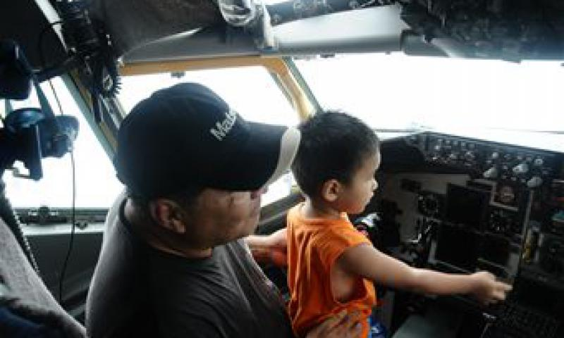 A Guam resident and his grandson sit in the pilot seat of a B-52 Stratofortress aircraft during the 2012 Andersen Air Force Base Open House in Guam Oct. 13. This year's open house is the first since 2009. (U.S. Air Force photo by Airman 1st Class Mariah Haddenham