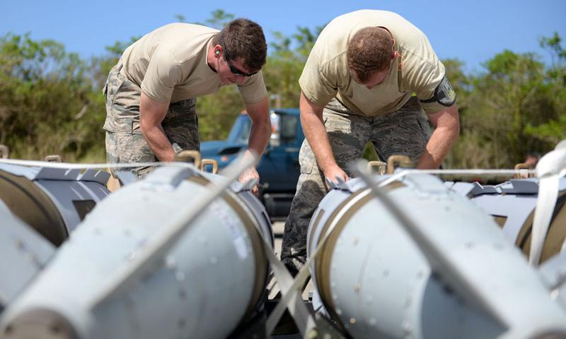 Staff Sgt. Nicholas Eder, 36th Munitions Squadron line delivery driver, and Tech. Sgt. Tyler Harrill, 7th Munitions Squadron munitions storage supervisor, tie down guided bomb units prior to delivering them to a weapons in-check station, June 1, 2015, Andersen Air Force Base, Guam. The 2015 Combat Ammunition Production Exercise included more than 250 Airmen from nine bases across the Pacific and U.S. (U.S. Air Force photo by Airman 1st Class Joshua Smoot)