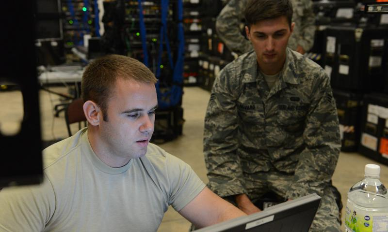(From left) Staff Sgt. Richard Rawls, cyber systems supervisor, and Senior Airman Garett Savard, cyber systems operator, both from the 644th Combat Communications Squadron, update programs on one of the three transportable base servers Jan. 13, 2014, on Andersen Air Force Base, Guam. The 644th CBCS became aligned with the 36th Contingency Response Group to be able to support missions with smaller airlift requirements and faster reaction capabilities. (USAF photo by Airman 1st Class Emily A. Bradley)
