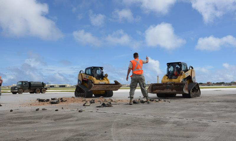 Staff Sgt. Austin Winegardner, 36th Civil Engineer Squadron project leader, directs Airmen operating heavy machinery to clear debris away from a simulated damaged area created during airfield damage repair training on the Andersen Air Force Base, Guam, flightline Jan. 23, 2014. The 36th Civil Engineer Squadron Airmen were the first in the Air Force to receive training on a new airfield damage repair capability. (U.S. Air Force photo by Airman 1st Class Emily A. Bradley)