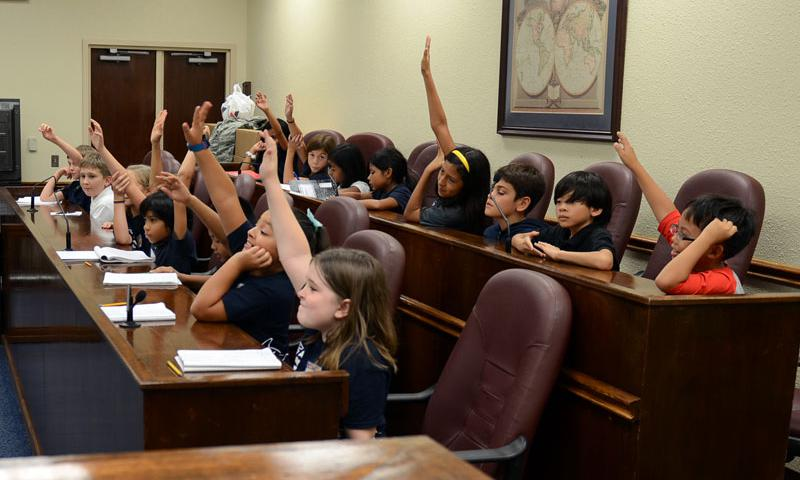 Andersen Elementary School fourth graders take part in the 36th Wing paralegal team's Alice in Wonderland-themed mock trial deliberation at the base courtroom May 1, 2015, at Andersen Air Force Base, Guam. This year, Law Day commemorated the 800th anniversary of the signing of the Magna Carta. (U.S. Air Force photo by Airman 1st Class Alexa Ann Henderson)