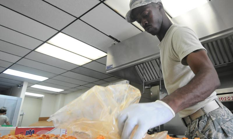 Staff Sgt. Wayne Collins, 36th Force Support Squadron food service supervisor, spreads chicken out evenly on a baking tray June 12, 2013, on Andersen Air Force Base, Guam. The Skyline Flight Kitchen prepares approximately 700 boxed lunches and 1,000 hot meals per week. (U.S. Air Force photo by Airman 1st Class Emily A. Bradley)