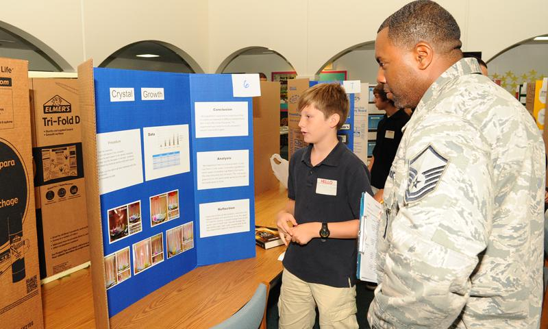 Master Sgt. Malik Franklin, 36th Munitions Squadron flight chief, listens to a seventh grader explain his science fair project at Andersen Middle School on Andersen Air Force Base, Guam, April 4, 2013. The science fair showcased the students' creativity and scientific knowledge. (U.S. Air Force photo by Airman 1st Class Adarius Petty)