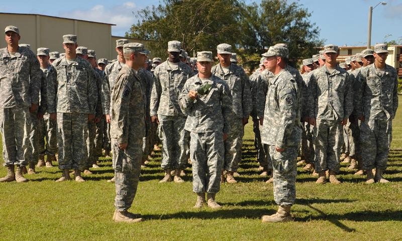 Cpt. Peter Lewall, commander (left), and 1st Sgt. Daryl Powell, senior enlisted leader (right), both of Alpha Battery, 2nd Air Defense Artillery Regiment (A-2), face each other in front of a troop formation as they prepare to begin uncasing their unit's guidon in a Transfer of Authority ceremony, Apr.1, 2014 at Andersen Air Force Base, Guam. The ceremony signaled the beginning of A-2's mission in Guam relieving A-4. (Photo by SrA Cierra Presentado, 36th Wing Public Affairs Office)