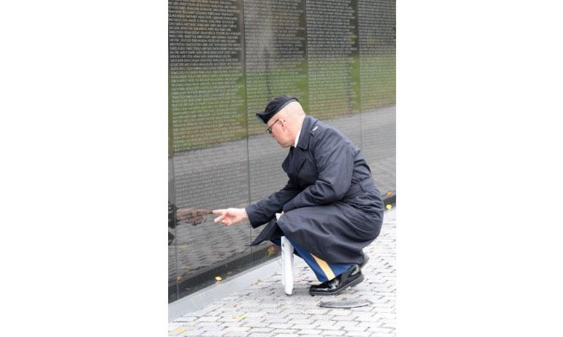 """Col. John Dowling, assigned to the Military Postal Agency in Crystal City, Virginia, takes a moment to find a name before participating in the in the """"Reading of the Names"""" event. In honor of their sacrifice, a group of volunteers paid tribute to those lost or missing in combat, as they collectively announce the names of all 58,318 service members inscribed on """"The Wall."""" (Photo Credit: U.S. Army photo by Devon L. Suits)"""