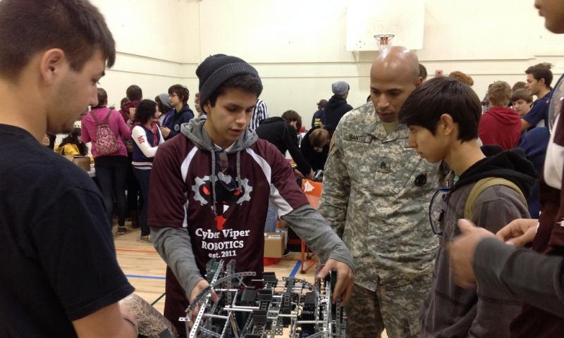 Staff Sgt. Rafael Santos with the Santa Clarita U.S. Army Recruiting Center helps students set up before the VEX Robotics Competition in Granada Hills, Calif., Nov. 23, 2013. U.S. ARMY