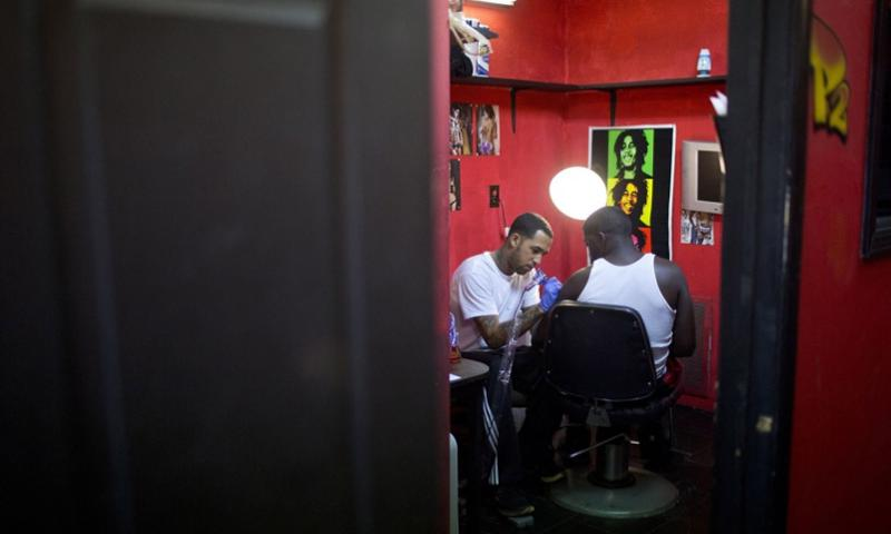 Army Pfc. Kevin Nixon, right, a Fort Bragg solider, watches as tattoo artist Brad Armstrong shades in a tattoo of a cross on Nixon's shoulder on Oct. 11, 2013, at Ink Well in Fayetteville, N.C. JILL KNIGHT, RALEIGH NEWS & OBSERVER/MCT