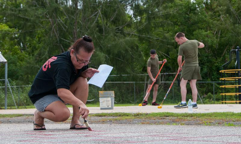 DEDEDO, Guam (Aug. 5, 2015) – Carmen Apellido, school aide, Juan M. Guerrero Elementary School, and Lance Cpls. David Belgard and Nicholas Wells, 31st Marine Expeditionary Unit (MEU), paint lines for hopscotch and other games during a community relations event at the school in Dededo Aug. 5. Sailors and Marines worked side-by-side with the school's employees in cleanup and beautification projects to prepare the facilities for the upcoming school year. (U.S. Navy photo by Leah Eclavea)