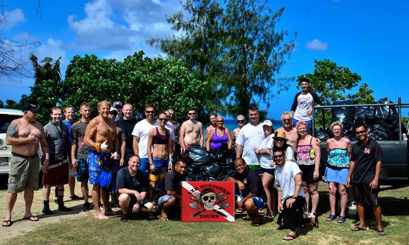 Love My Ocean event participants pose alongside bags of trash that they removed from the Agat Cemetery beach and Amtrack dive site.  Over 40 large bags were filled and removed from the site, along with other large debris, including a big-screen TV that had been illegally dumped along the beach.