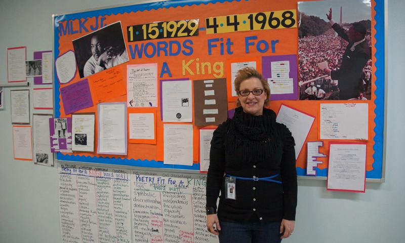 Joan Hodges, the 6th grade Language Arts teacher at Yokota Middle School, stands in front of her student's word wall which highlights the life of Martin Luther King, Jr.
