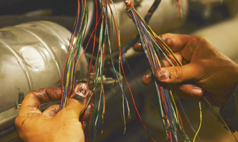 Tech. Sgt. Ryan Trandell, 36th Communications Squadron cable and antenna maintenance shop Cable Dawgs technician, works on telephone wire inside the cable vault on Andersen Air Force Base Nov. 19. The Cable Dawgs are responsible for maintaining more than 33,000 feet of copper lines and 97 fiber-optic cables on Andersen. U.S. Air Force photo by Senior Airman Benjamin Wiseman