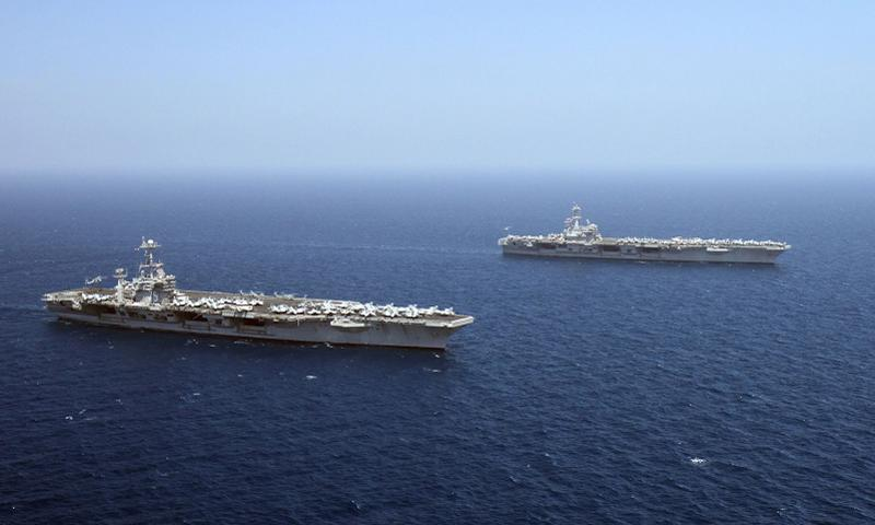 The Nimitz-class aircraft carriers USS Harry S. Truman (CVN 75), left, and USS George H.W. Bush (CVN 77) transit during a turnover of responsibility in the Gulf of Aden. George H.W. Bush is taking over support of maritime security operations and theater security cooperation efforts in the U.S. 5th Fleet area of responsibility. Juan David Guerra/U.S. Navy