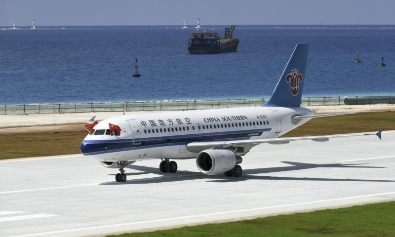 Chinese national flags fly from the cockpit windows of a China Southern Airlines passenger jet after it successfully test-landed on the Meiji reef of the Nansha Islands in the South China Sea on July 13, 2016. China said Monday, July 18, 2016, that it is closing off a part of the South China Sea for military exercises this week.  Chen Yichen/Xinhua via AP