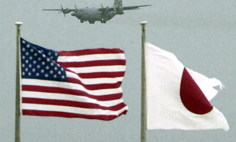 U.S. and Japanese flags flutter in the wind at Kadena Air Base on Okinawa, Japan. A Navy effort to test a cloud-based technology for mobile phones to make it easier to have volunteers take turns driving drunk friends home, could help ease tensions on Okinawa. 	 Kyodo News/AP