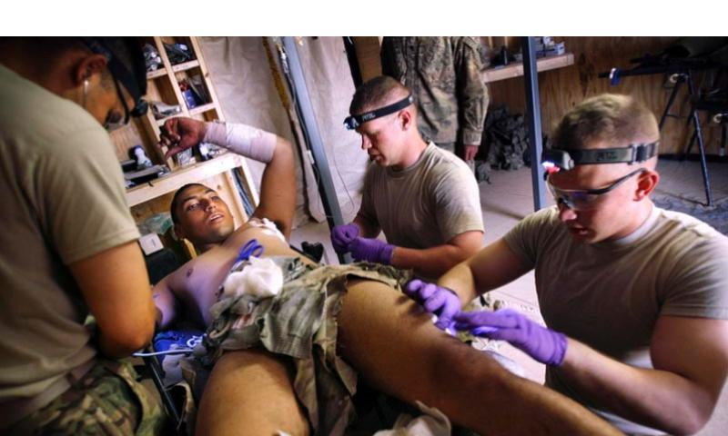 Spc. Victor Bardales is treated for shrapnel wounds by medics Sgt. Joe Tapia, left, Sgt. Miles Boggs and Pfc. Nicholas Seay from a rocket-propelled grenade attack in May, near Combat Out Post Nalgham, Afghanistan. Laura Rauch/Stars and Stripes  Laura Rauch/Stars and Stripes