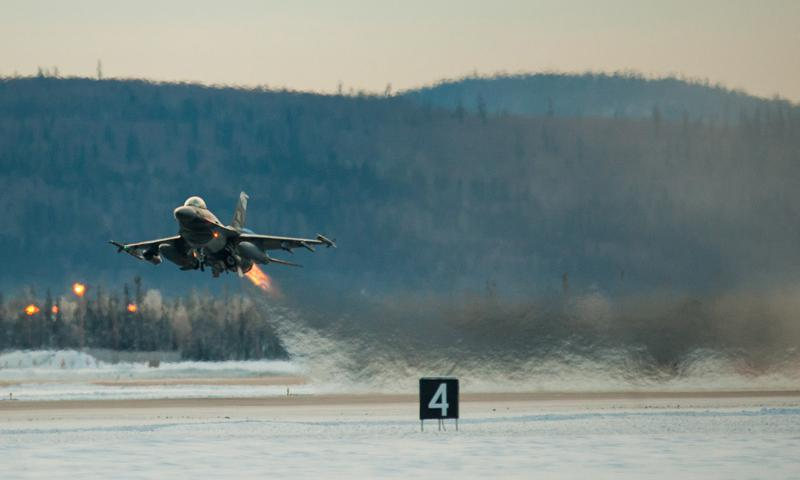 One of 14 U.S. Air Force F-16 Fighting Falcon aircraft with the 18th Aggressor Squadron takes off from Eielson Air Force Base, Alaska, shortly after sunrise Jan. 17, 2015, in transit to Joint Base Pearl Harbor-Hickam, Hawaii, and Andersen Air Force Base, Guam, to participate in Pacific Air Forces exercises.  (U.S. Air Force photo by Tech. Sgt. Joseph Swafford)