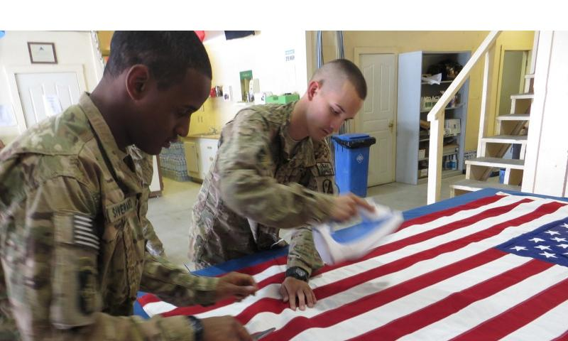 Pfc. Durell Siverand, left, and Pfc. Alex Valdivia, mortuary affairs specialists with the 54th Quartermaster Company, prepare a flag that will cover a transfer case carrying the remains of a U.S. servicememberfrom Bagram Air Field in Afghanistan to Dover Air Force Base in Delaware.   Martin Kuz/Special to Stars and Stripes