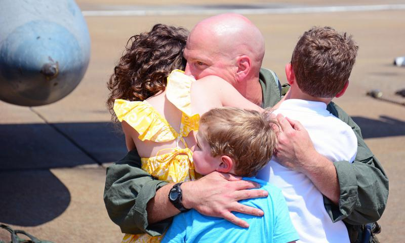Cmdr. Marvin Scott, assigned to Strike Fighter Squadron 83, reunites with his family during a homecoming celebration at Naval Air Station Oceana on July 12, 2016. The squadron returned after an eight-month deployment as part of the USS Harry S. Truman Carrier Strike Group. 	 Kayla King/U.S. Navy