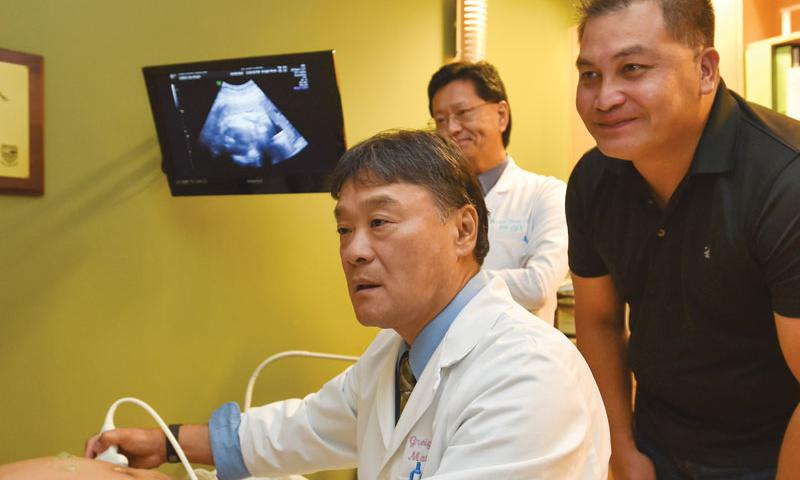 Dr. Greigh I. Hirata performs an ultrasound exam as James B. Doyle, right, and Dr, Thomas Shieh look on at Shieh's clinic in Tamuning on Sept. 6. Photo by Frank San Nicolas, Pacific Daily News via AP