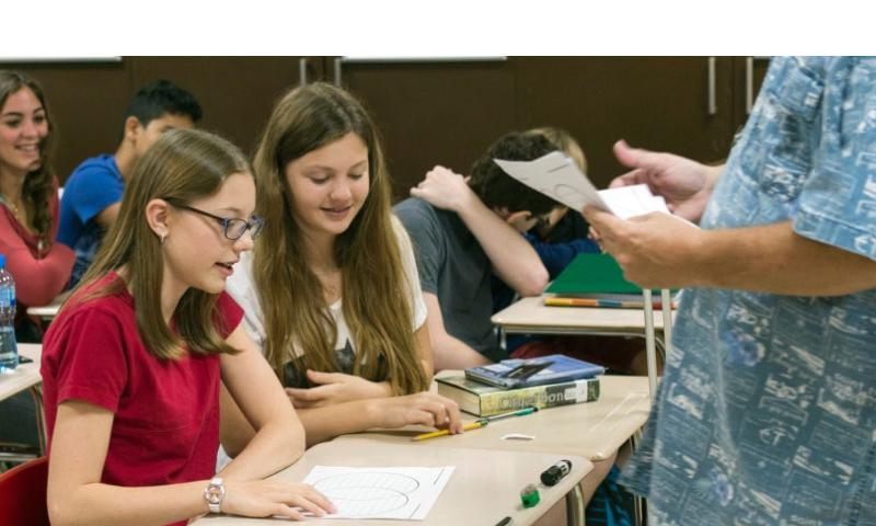 Haley Rowe, left, an eighth-grade student at the Bahrain school, and classmates begin work on an assignment handed out by their teacher, Tim Falls, Thursday, Aug. 27, 2015. Classes started earlier this week at the Bahrain School.    Chris Church/Stars and Stripes