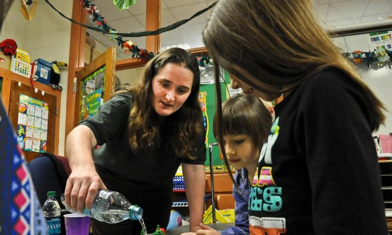 Magen McCollough, Williamsburg Environmental Group civil engineer, pours water over a simulated habitat to show the effects of water runoff during the Introduce a Girl to Engineering Day at John H. Russell Elementary School in Quantico, Va., in February 2012. The Pentagon has asked the RAND Corp. to study whether the DOD still needs to run schools in the United States. Photo courtesy of the U.S. Marines