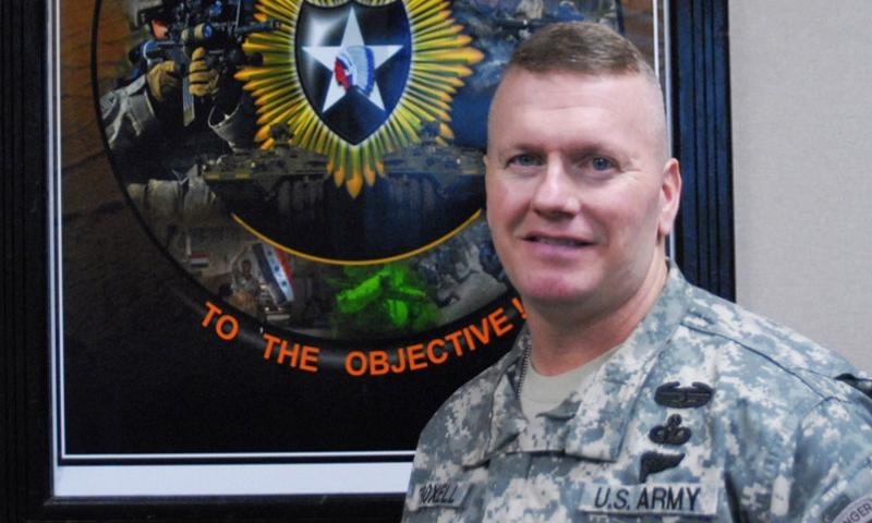 Command Sgt. Maj. John Troxell in front of his poster commemorating his service with the 4th Stryker Brigade.  U.S. Army