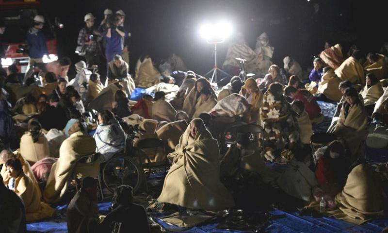 People are seen at a parking lot in Mashiki, Kumamoto Prefecture, Japan, at 1:12 a.m. on Friday after evacuating their homes.     The Japan News/Yomiuri