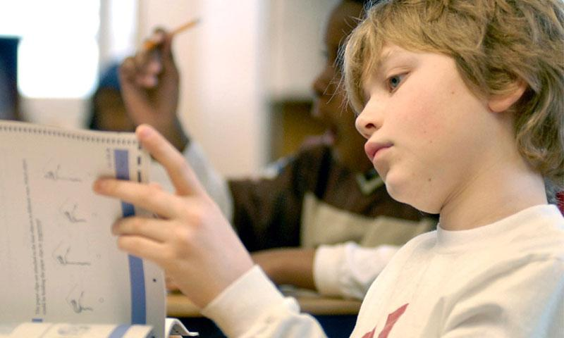 A fifth-grader at Landstuhl Elementary and Middle School, Germany, looks through his TerraNova test. Scoring discrepancies in the spring standardized assessment have delayed the release of results for some 33,000 DODEA students. STARS AND STRIPES